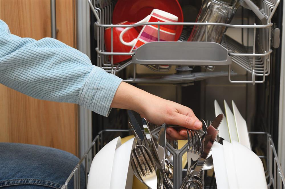 female taking clean dishes out of dishwasher