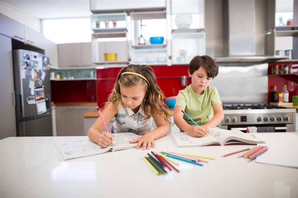 siblings doing homework in the kitchen